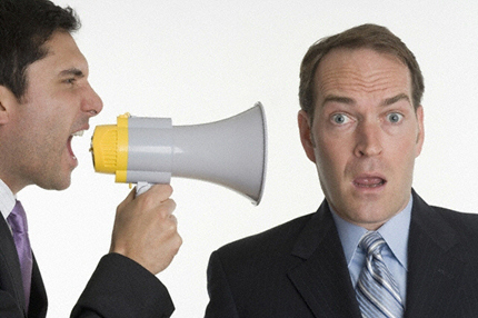 Person with bullhorn yelling at a surprised person